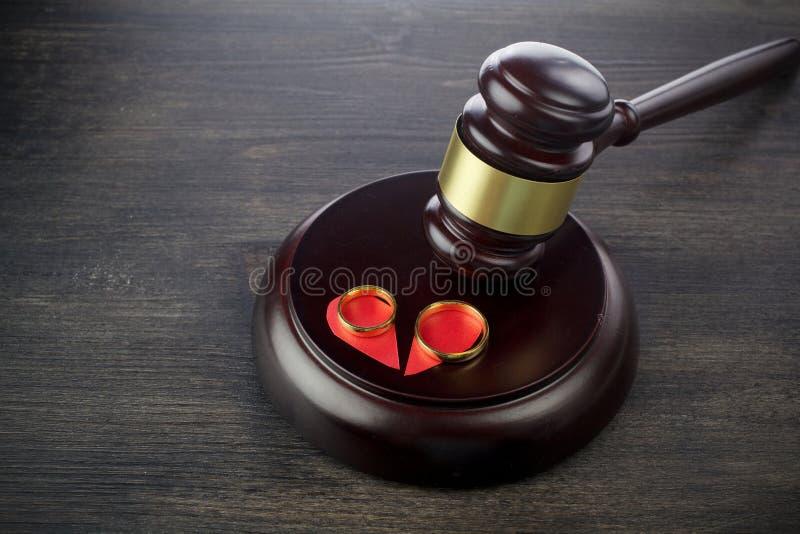Молоток обручальных колец судьи на темной деревянной предпосылке Продолжения развода стоковая фотография