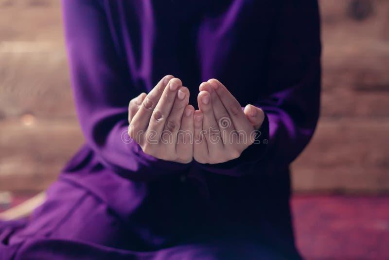 Моля молодая мусульманская женщина Ближневосточная девушка моля и читая святой Коран Мусульманская женщина изучая Коран стоковые изображения