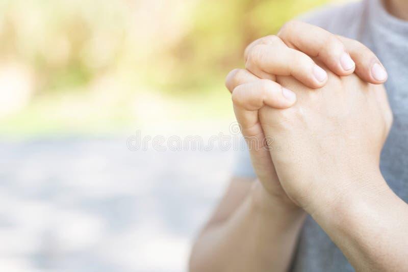 Моля руки верных зрелых рук молодого человека сложенных в поклонении на на открытом воздухе стоковые фотографии rf