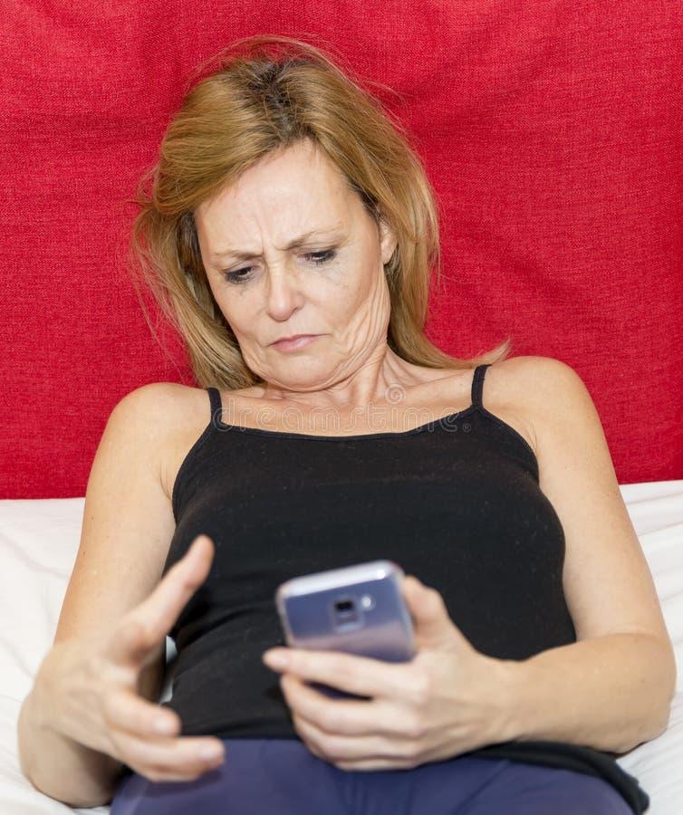 Момент отчаяния женщины которая смотрит дисплей ее смартфона стоковая фотография rf