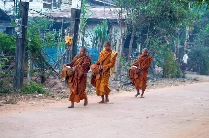Монахи идут в раннее утро в деревне Isan в провинции Sakon Nakhon, Таиланде стоковая фотография