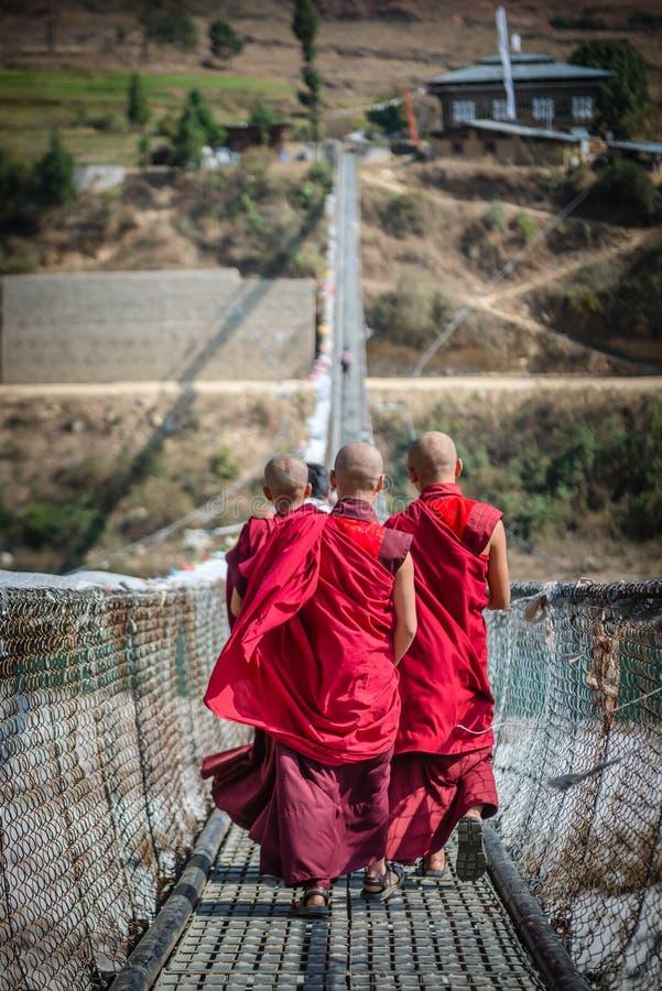 Монахи или хорошо знают как лам в Тибете идя на мост, Бутан стоковое изображение