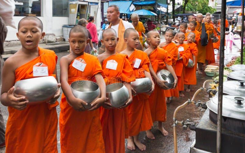 Монахи послушника собирая милостыни на рынке в старом городке Пхукета, Таиланде стоковое фото rf