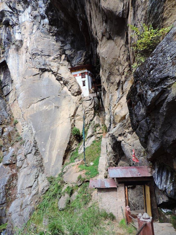 Монахи самонаводят между утесами на пути к Paro Taktsang Бутана стоковое фото