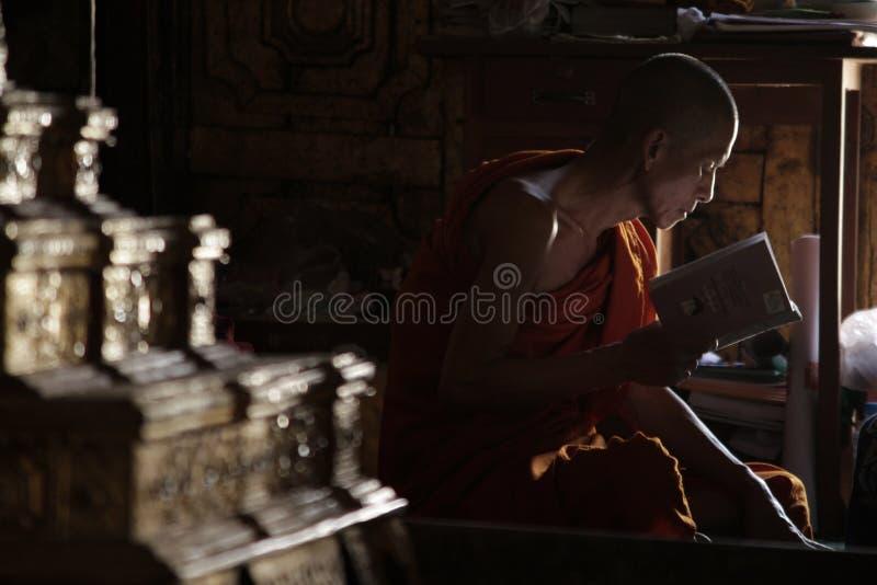 Монахи сидели тихо читающ книгу стоковые изображения