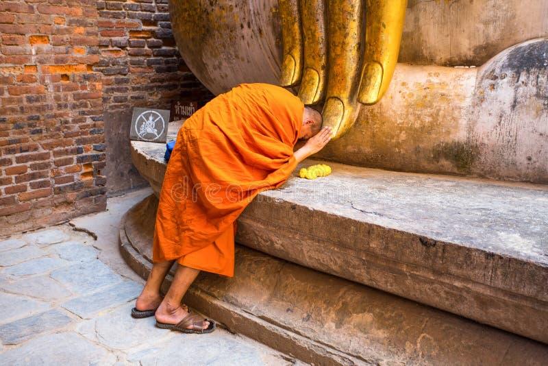 Монах молит под большой статуей Будды приятеля Sukhothai Wat Si, Таиланда стоковая фотография