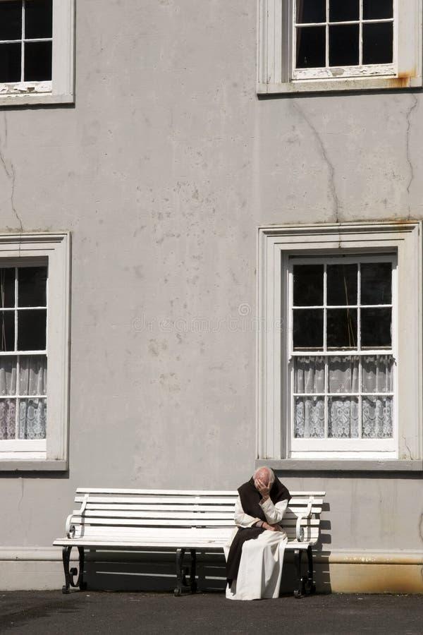 Монах усаженный на стенд в тихом раздумье стоковая фотография rf