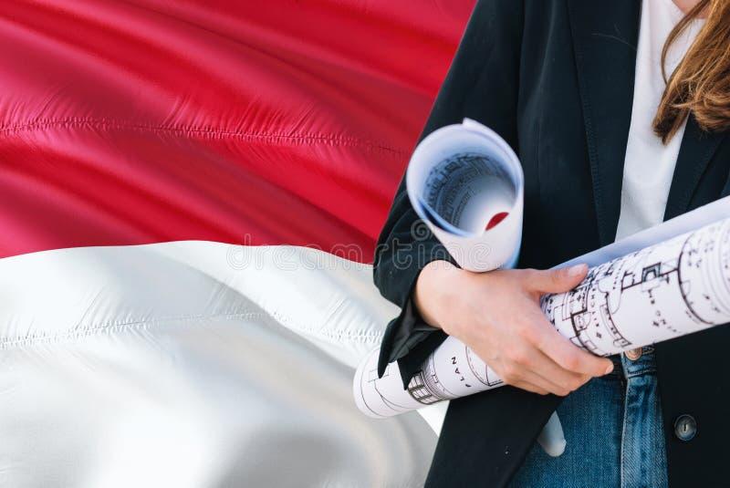 Монегаскская светокопия удерживания женщины архитектора против предпосылки флага Монако развевая Концепция конструкции и архитект стоковое фото