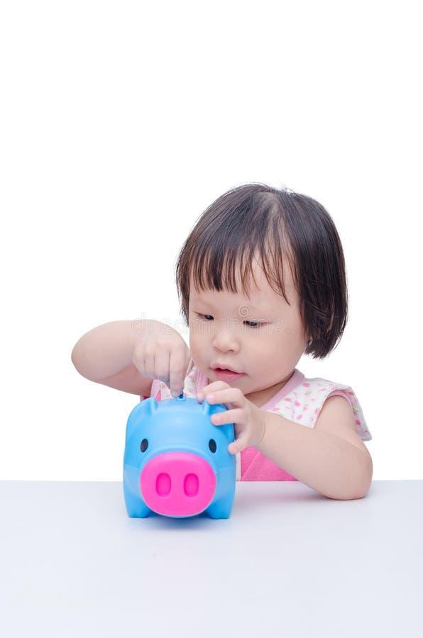Монетка вставки девушки в копилку стоковая фотография rf