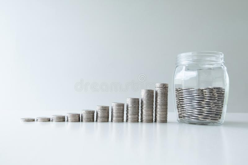 Монетка в банке стеклянной бутылки с диаграммой роста бара монеток, шагом вверх по началу вверх по делу к успеху, сохраняя деньга стоковые изображения