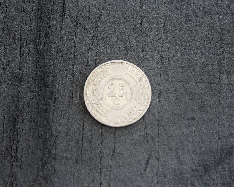 монетка гульдена Нидерланд цента 25 (двадцать пять) Antillean на черной предпосылке стоковое изображение rf