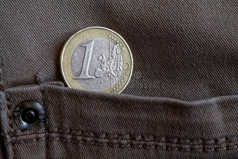Монетка евро с деноминацией 1 евро в карманн коричневых джинсов джинсовой ткани стоковая фотография