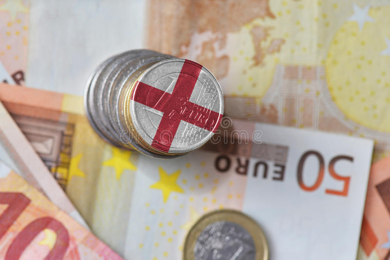 Монетка евро с национальным флагом Англии на предпосылке банкнот денег евро стоковое фото