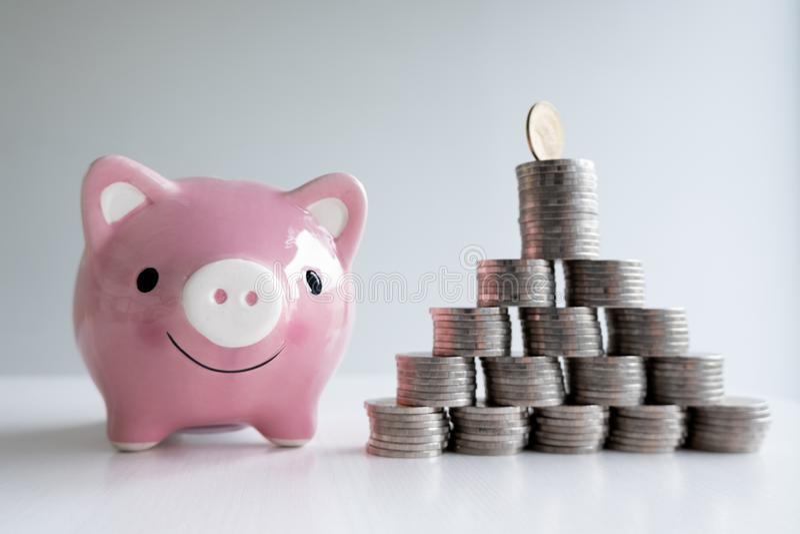 Монетка и банк сохранения пинка piggy с пирамидой монеток стоковое фото