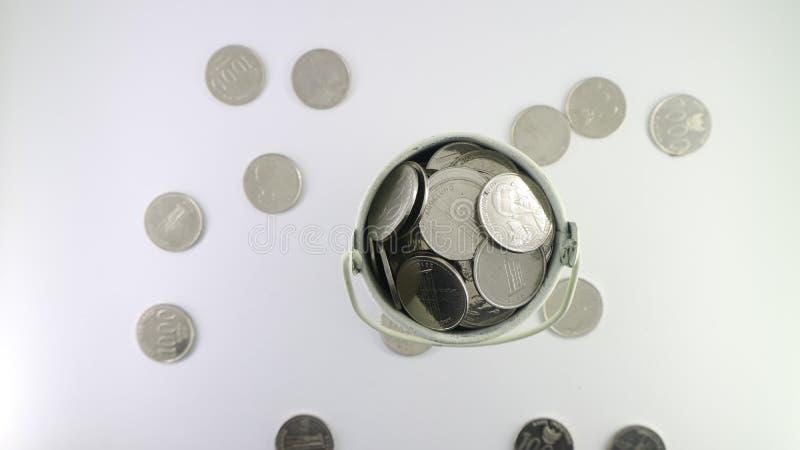 Монетка на белом ведре на белой предпосылке стоковая фотография rf