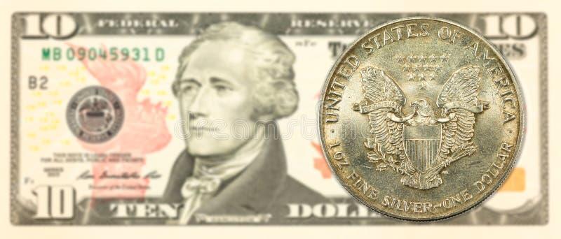 1 монетка серебряного доллара Соединенных Штатов против примечания 10 долларов США стоковая фотография