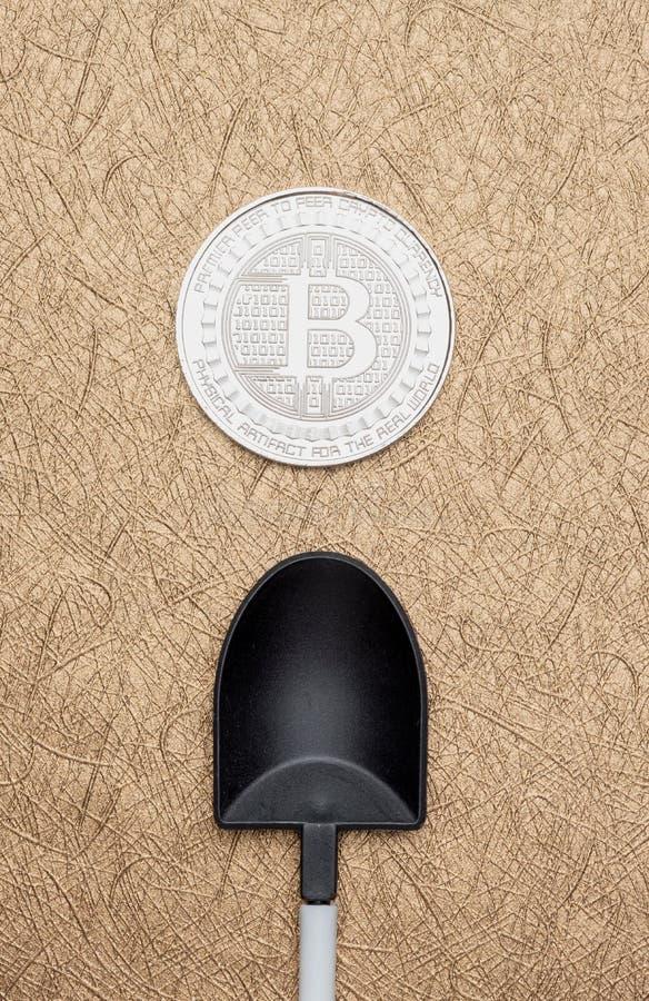 Монетка серебряных bitcoins взгляд сверху секретная над черным лопаткоулавливателем на золотом стоковые изображения