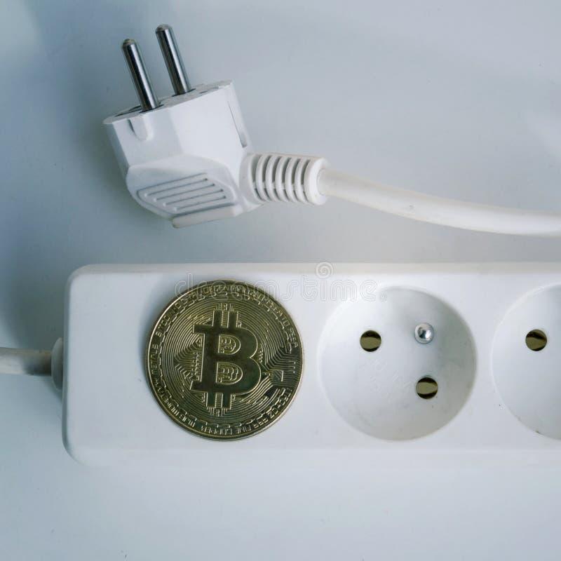 Монетка Bitcoin лежа на удлинителе с 2 пустыми гнездами, cryptocurrency инвестируя, следе ноги прокладки силы энергопотребления стоковая фотография