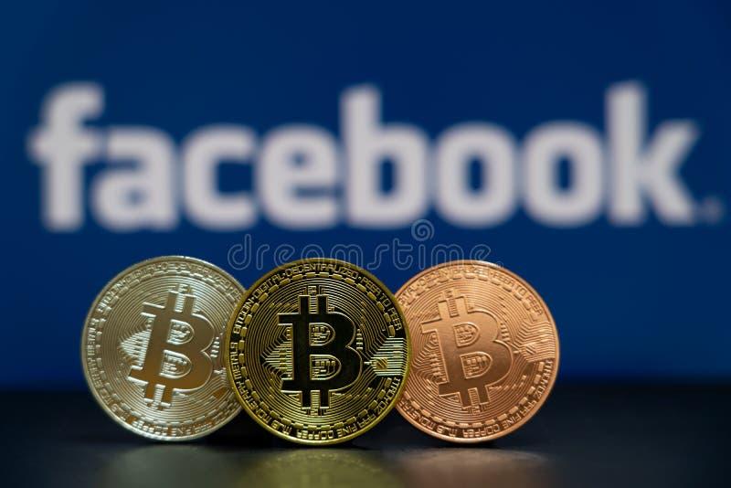 Монетка Bitcoin с экраном логотипа Facebook голубым стоковое фото rf