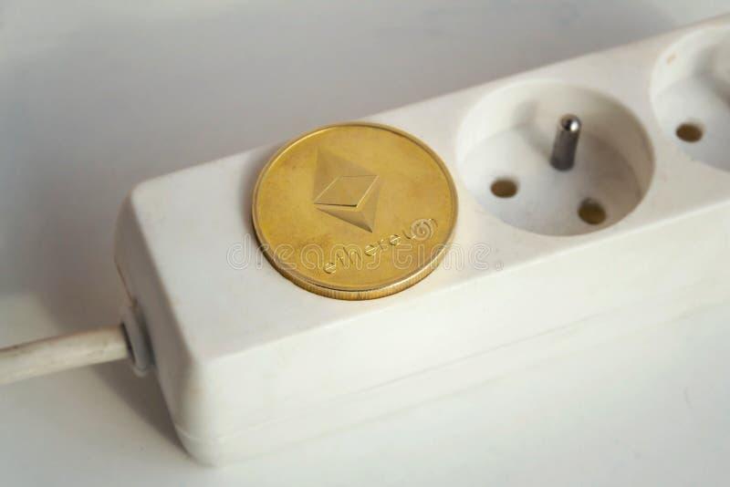 Монетка Ethereum лежа на удлинителе прокладки силы с пустыми гнездом, энергопотреблением cryptocurrency и концепцией следа ноги стоковые фотографии rf