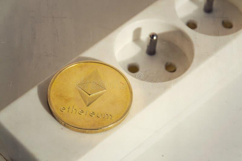 Монетка Ethereum лежа на удлинителе прокладки силы с пустыми гнездом, энергопотреблением cryptocurrency и концепцией следа ноги стоковое изображение rf