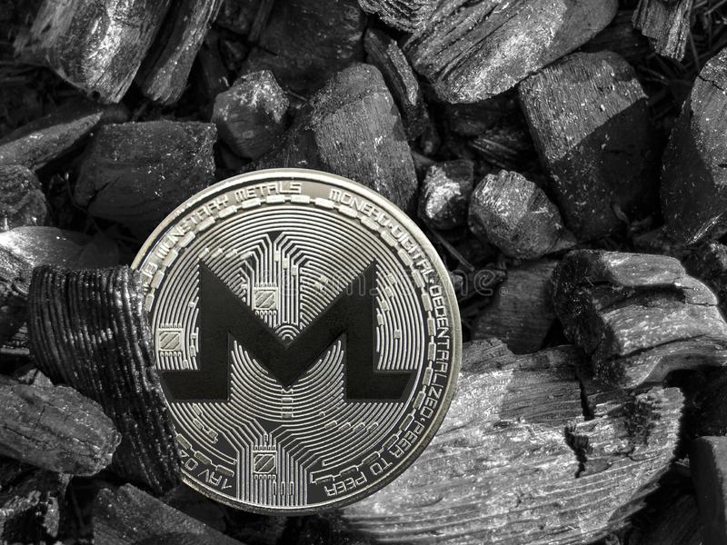 Монетка xmr Cryptocurrency лежит на угле Минирование и энергия для минировать стоковое изображение rf