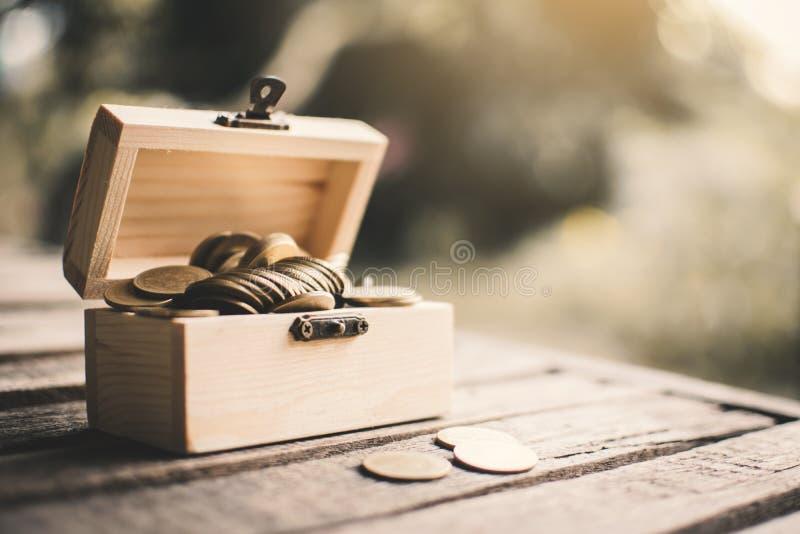 Монетки в деревянной коробке стоковые изображения