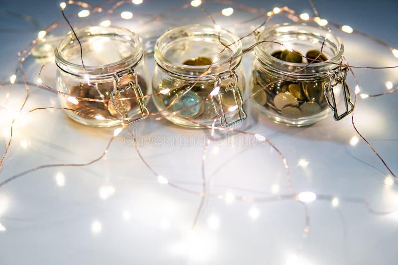 Монетки в опарнике валюты стеклянном со светами рождества стоковое фото rf