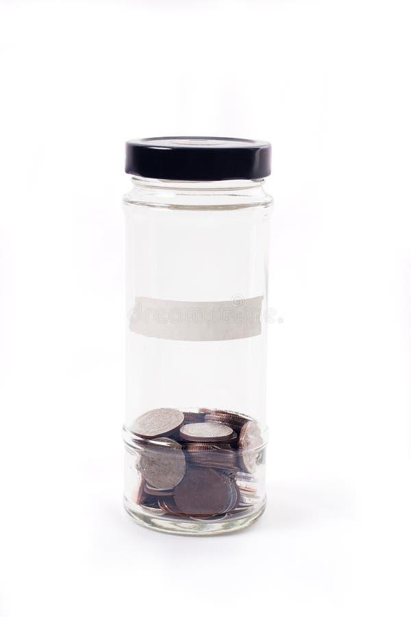 Монетки в стеклянном опарнике на белой предпосылке для финансов сбережений денег стоковые фото