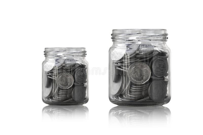 Монетки в стеклянном опарнике против, сбережения чеканят - концепция денег сбережений концепции вклада и интереса стоковые фотографии rf