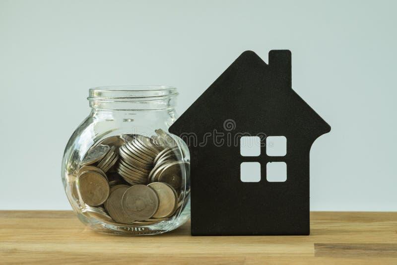 Монетки в стеклянном опарнике с бумажным домом на деревянном столе как финансовый стоковая фотография rf
