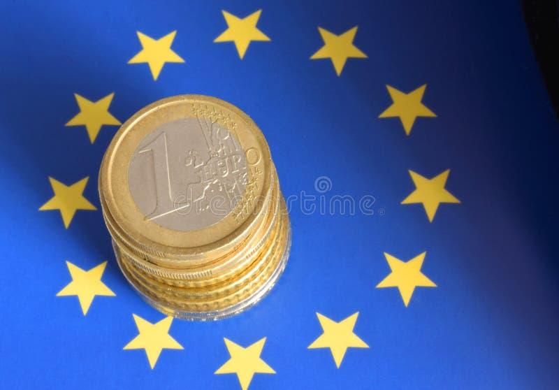 Монетки евро на флаге Европейского союза стоковое изображение