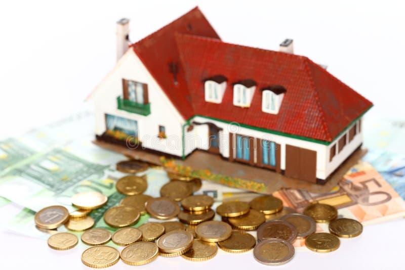 Монетки денег и модель дома стоковые изображения rf