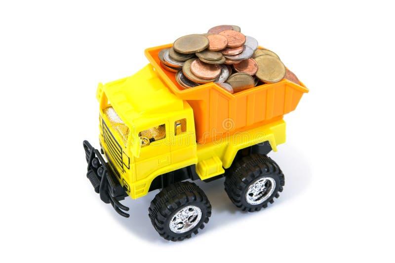Монетки загрузки игрушки тележки Dumper изолированные на белой предпосылке Деньги монеток нагрузки игрушки тележки грузовика стоковое изображение