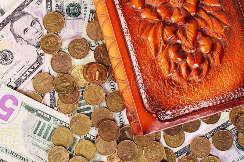Монетки и банкноты в коробке стоковая фотография