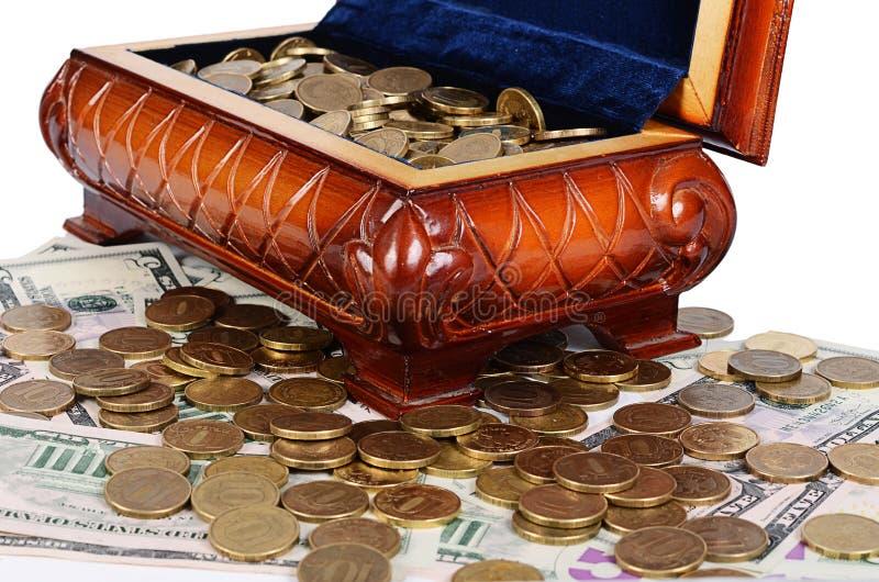 Монетки и банкноты в коробке стоковое фото