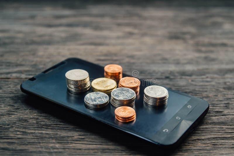 Монетки и деньги тайского бата на умном телефоне стоковое фото rf