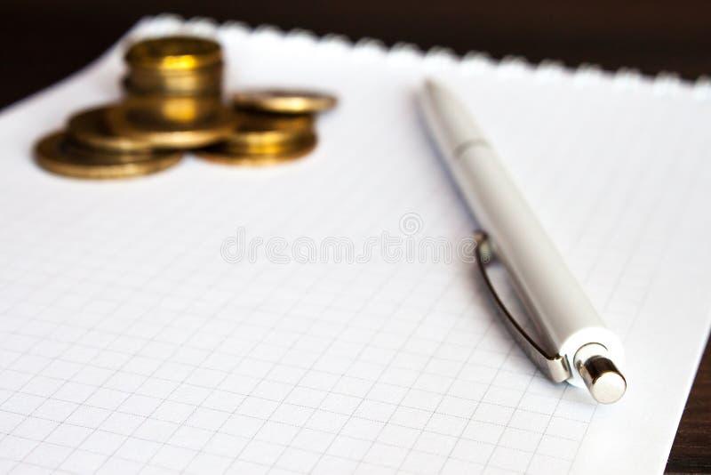 Монетки и ручка стоковое фото rf