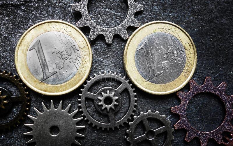 Монетки и шестерни евро стоковые фото