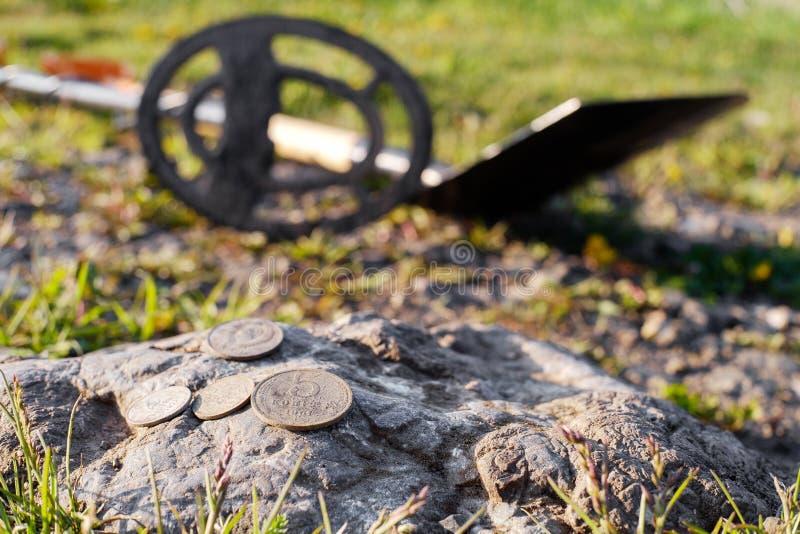 Монетки найденные в земле расположены на пакостном камне, предпосылка металлоискатель стоковые изображения