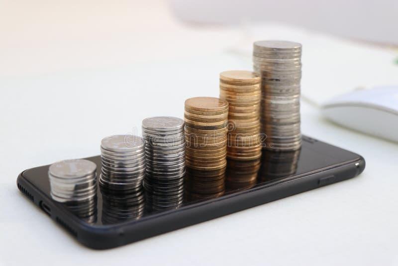 Монетки на мобильном телефоне увеличивают, и удельный вес на рынке передвижной оплаты получает большле и большле стоковая фотография
