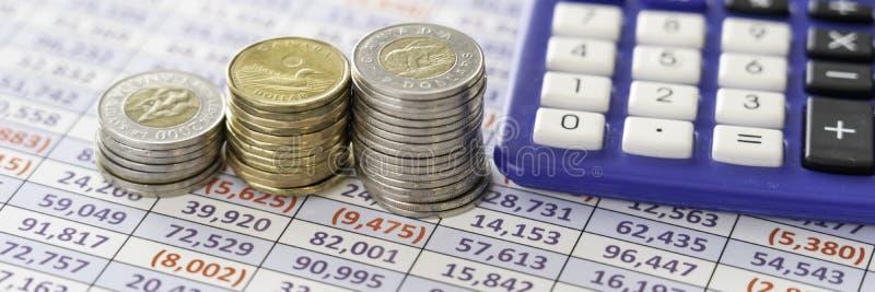 Монетки на отчете об электронной таблицы для того чтобы высчитать выгоды стоковая фотография rf