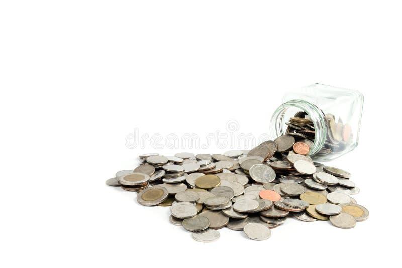 Монетки разливая из стеклянного опарника стоковая фотография