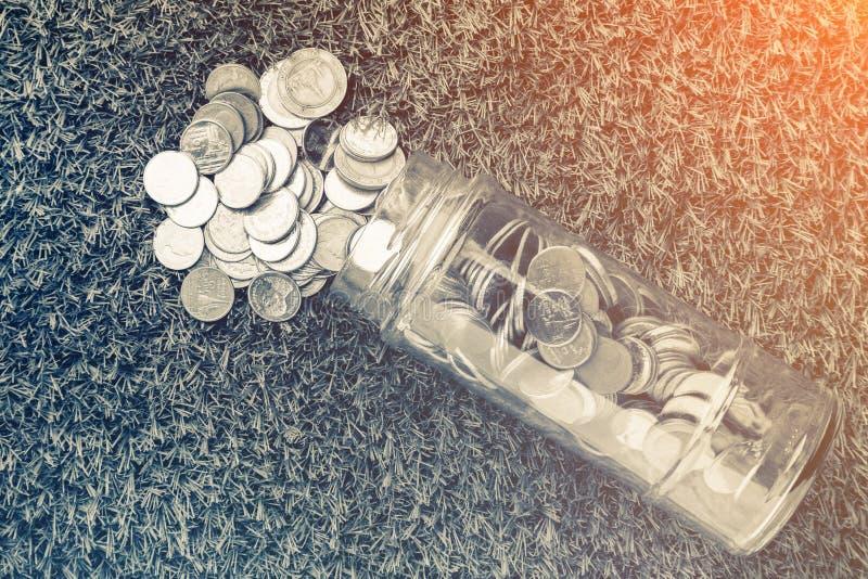Монетки разливая из стеклянной бутылки с влиянием фильтра стоковые изображения