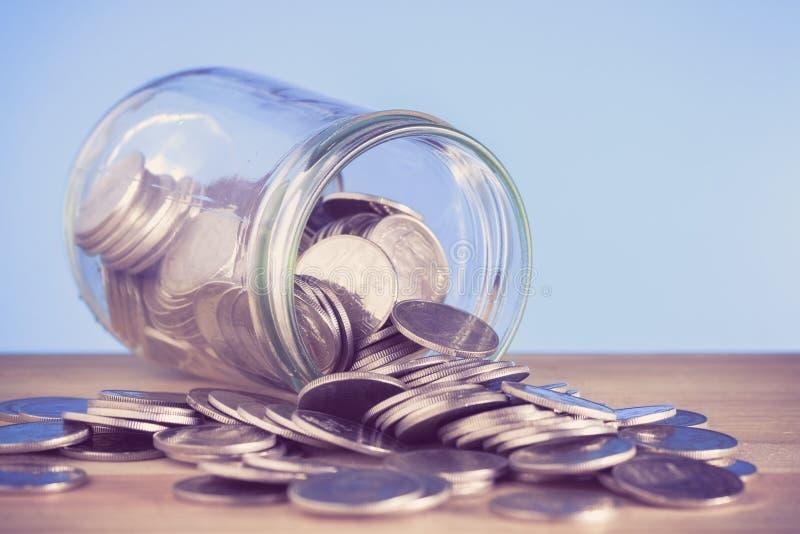 Монетки разливая из стеклянной бутылки стоковые изображения