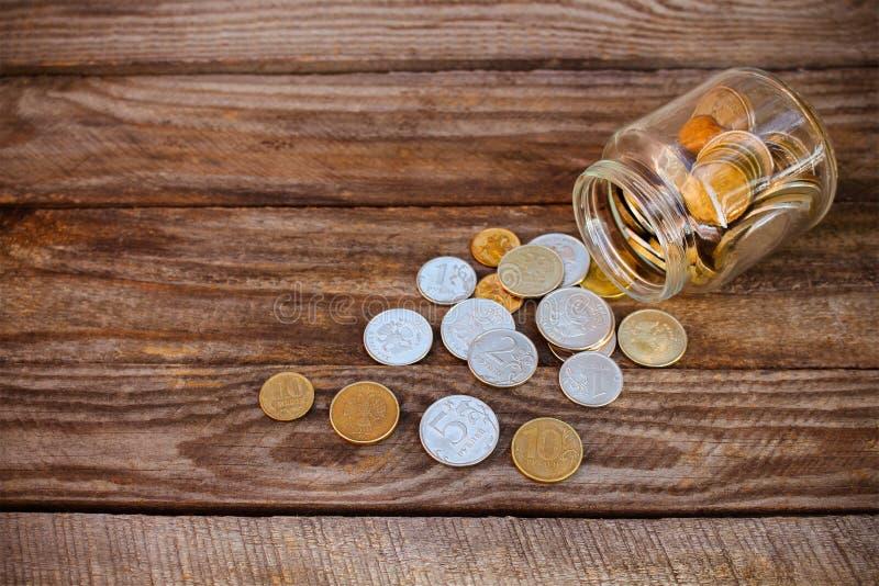Монетки разливая от стеклянного опарника стоковые изображения