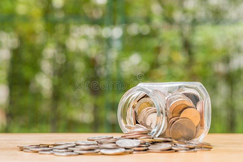 Монетки тайского бата разливая из опарника денег стоковое фото