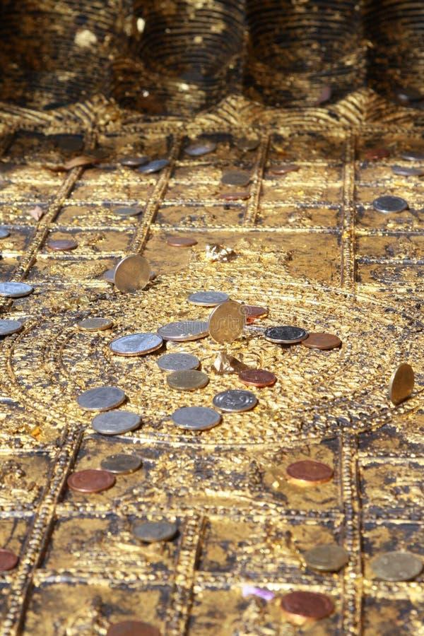 Монетки установленные на след ноги Будды стоковые фото