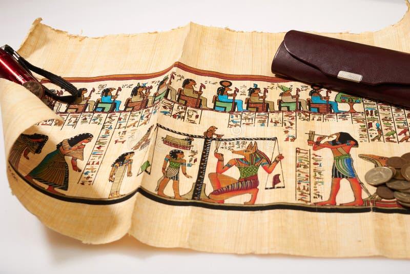 Монетки, электрофонарь и египетский папирус стоковые фото