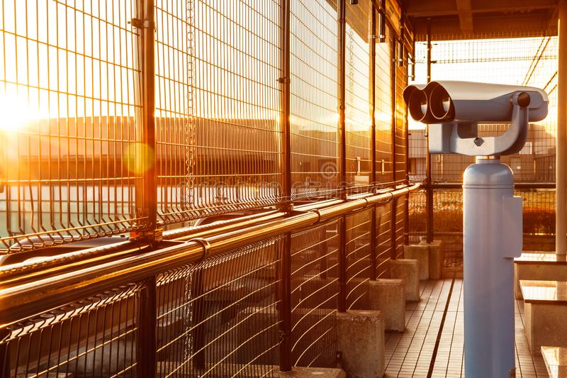 Монетк-работаемые бинокли или телескоп в накалять утра золотой светлый для туристов для того чтобы наблюдать плоскими взлетами и  стоковое изображение rf